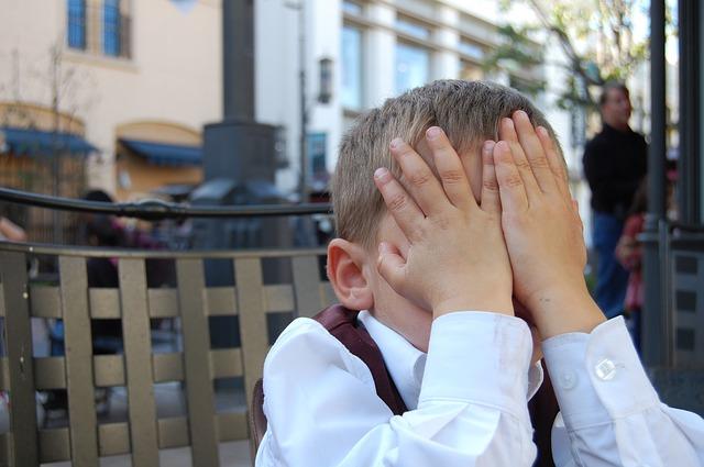 手で顔を隠す子
