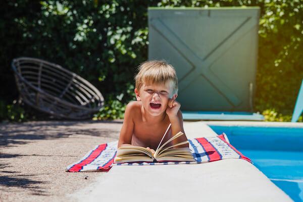 プールサイドで読書する男の子