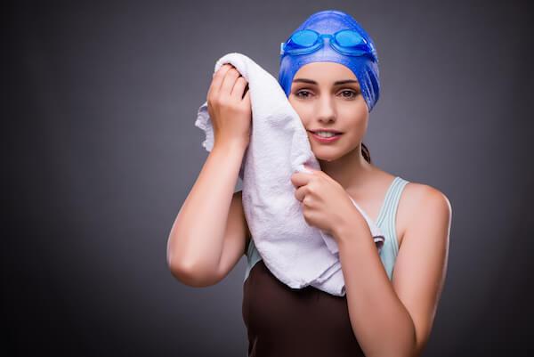 タオルで顔を拭く女性スイマー