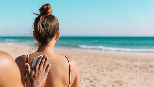 女性の背中に日焼け止めを塗る